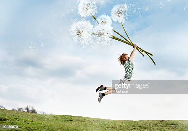 Boy being lifted into the air holding dandelions