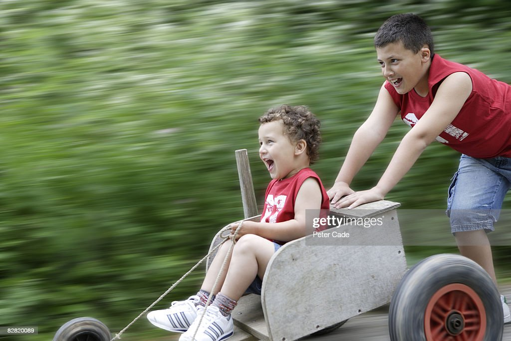 boy being pushed in go kart by brother : Stock Photo