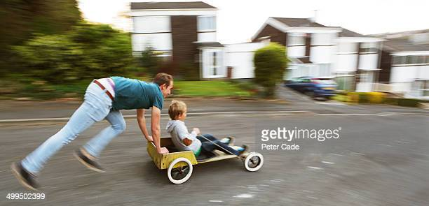 Boy being pushed on homemade go kart