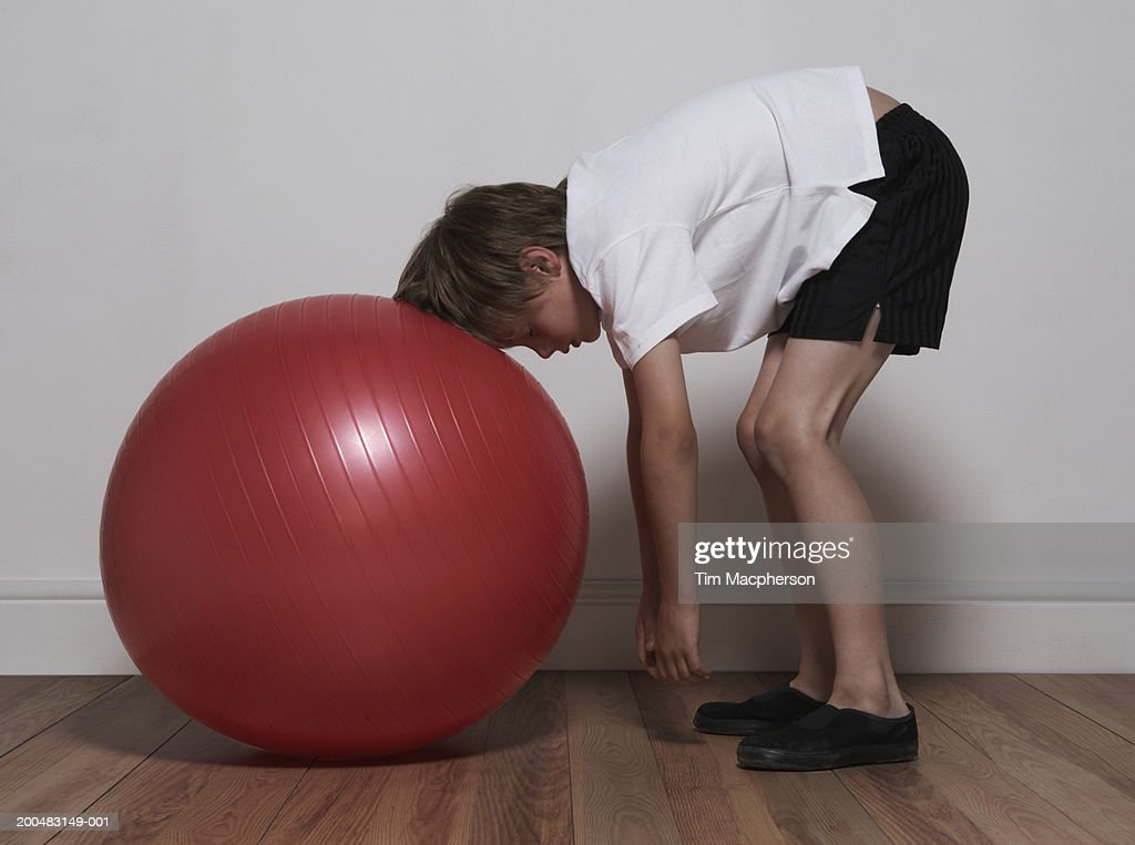 Boy (6-8) bending over with head resting on exercise ball, indoors, side view