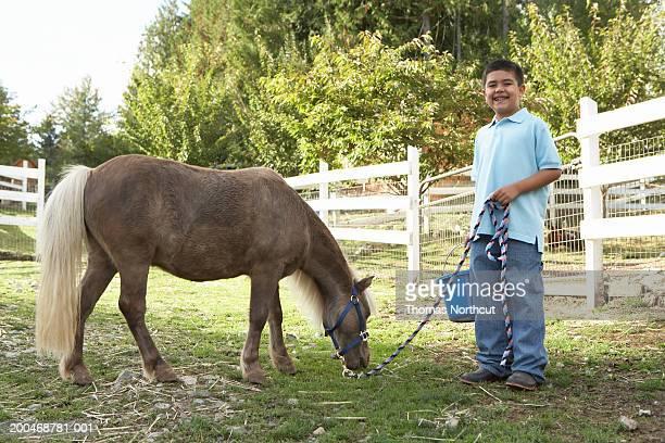 Boy (7-9) beside Shetland pony in pasture, portrait