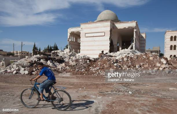 A'ZAZ ALEPPO SYRIA A boy bicycles by a damaged mosque in A'zaz Syria