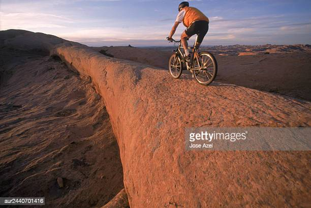 A boy biking on an uneven mountainous area, Utah, USA.