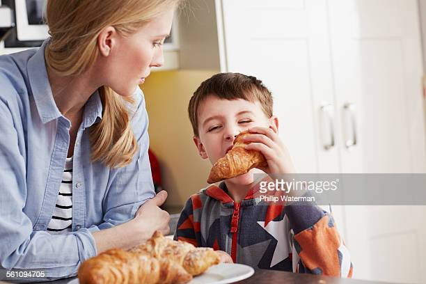 Boy biting croissant, mother watching