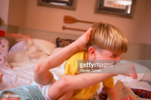 Boy biting little girls foot in bed stock photo getty images for Boys and girls in bed