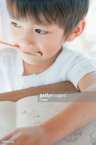 A boy(4-5) biting pencil, close-up