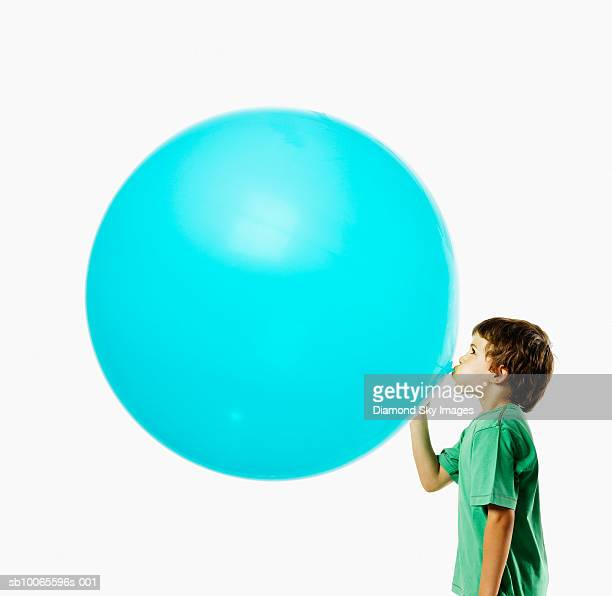 Boy (6-7) blowing balloon, side view