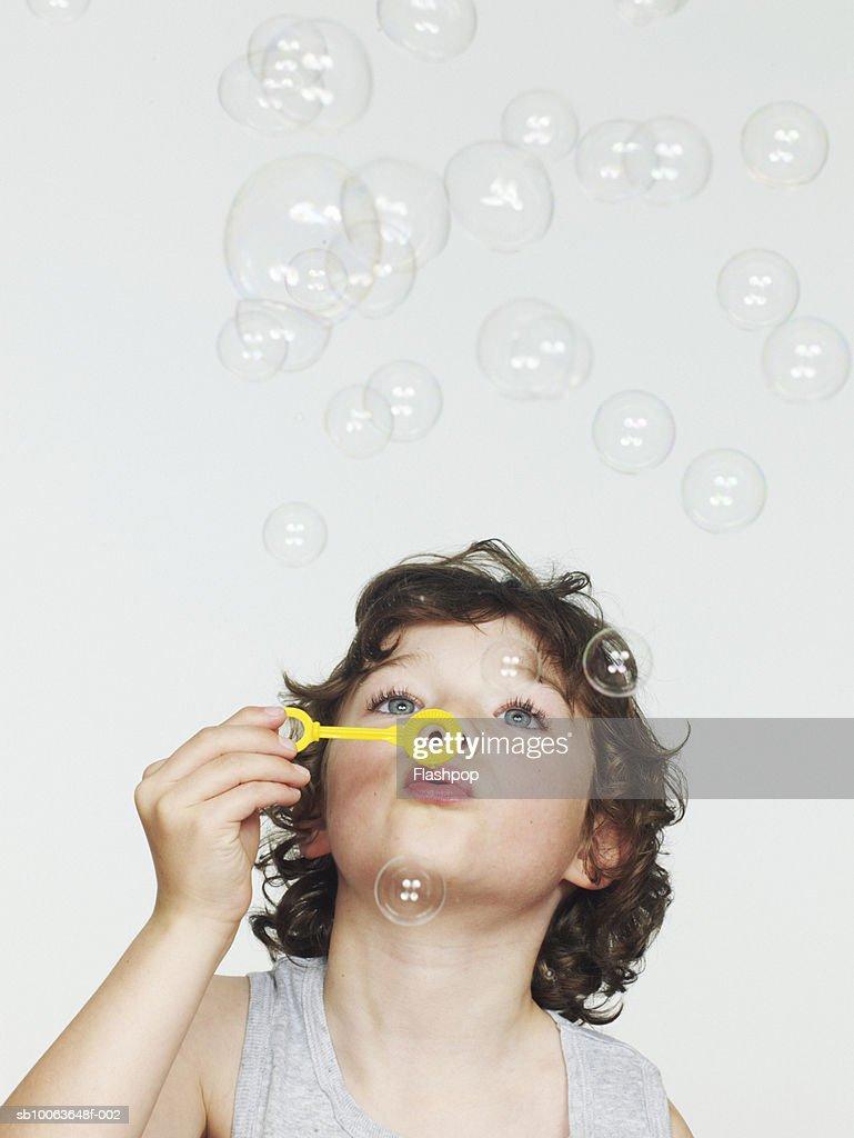 Boy (6-7) blowing bubbles, close-up