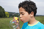 Boy (7-9) blowing bubbles in field