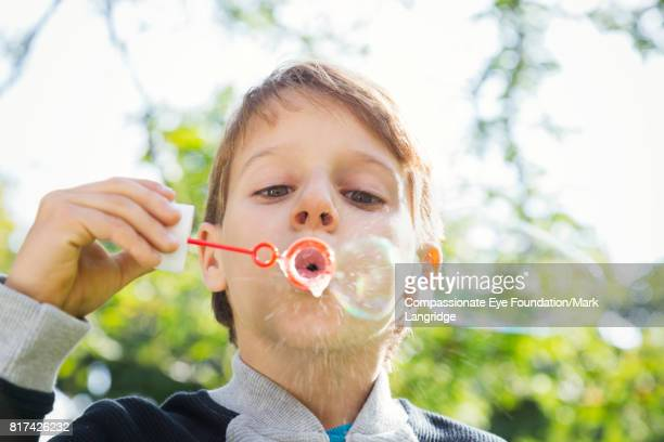 Boy blowing bubbles in garden