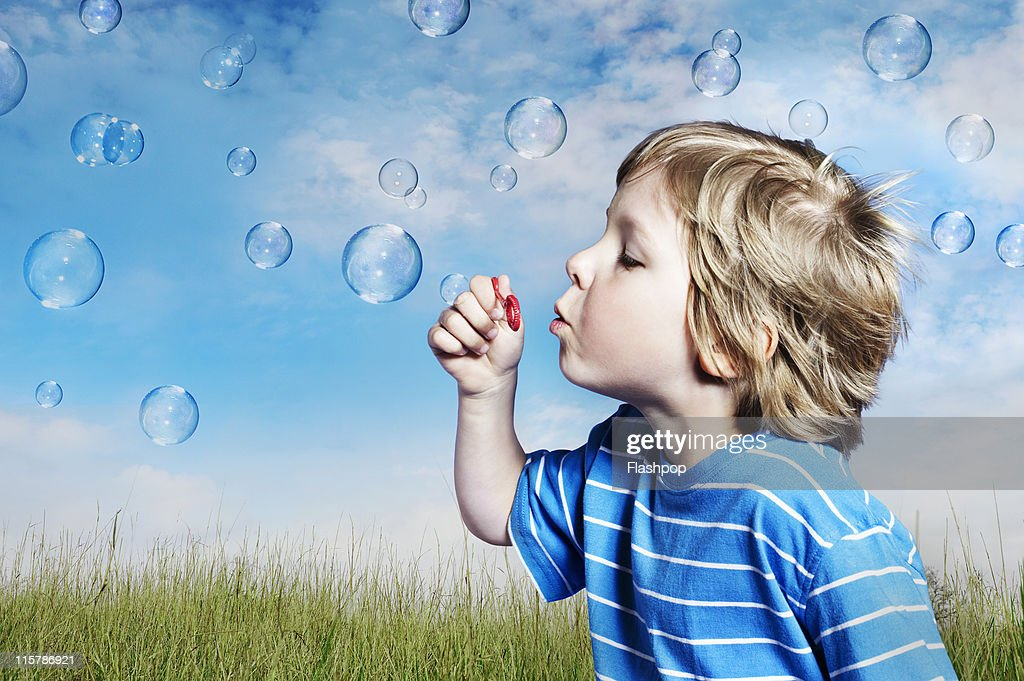 Boy blowing bubbles : Stock Photo
