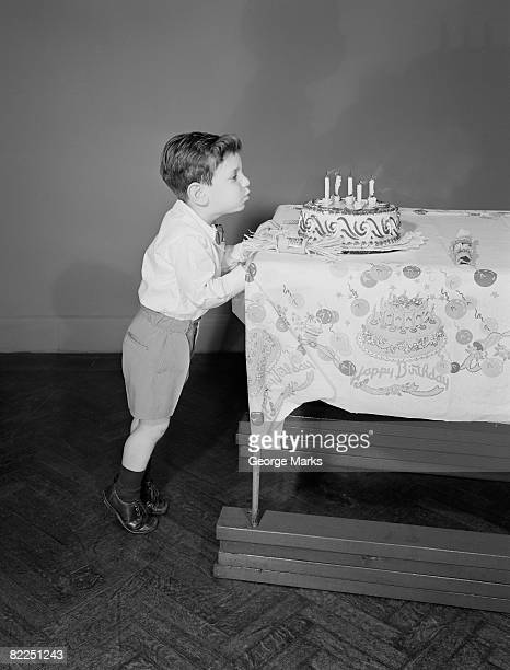 Garçon (6-7) souffler les bougies sur le gâteau d'anniversaire