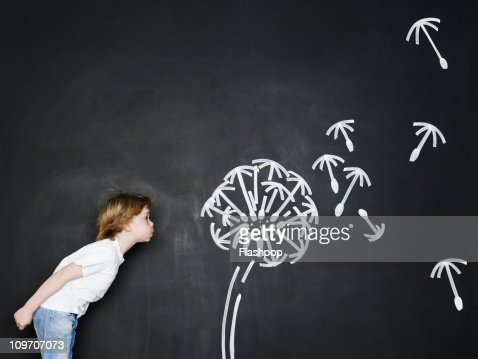 Boy blowing dandelion clock : Stock Photo