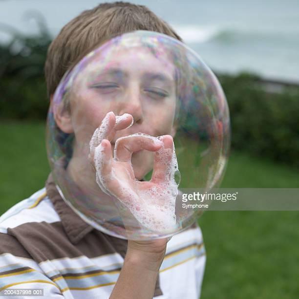 Boy (11-13) blowing large soap bubble