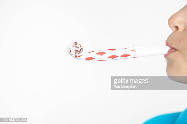 Boy (10-12) blowing noisemaker, side view, mid section