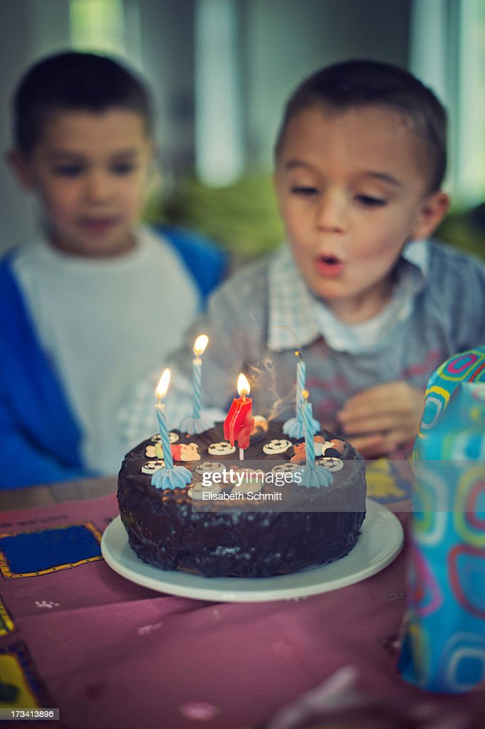 Boy blowing out birthday candles on cake : Stock Photo