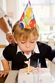 Boy blowing out birthday candles