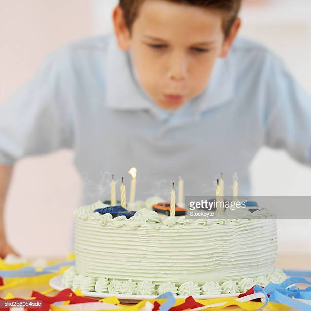 Boy (9-10) blowing out candles on a birthday cake