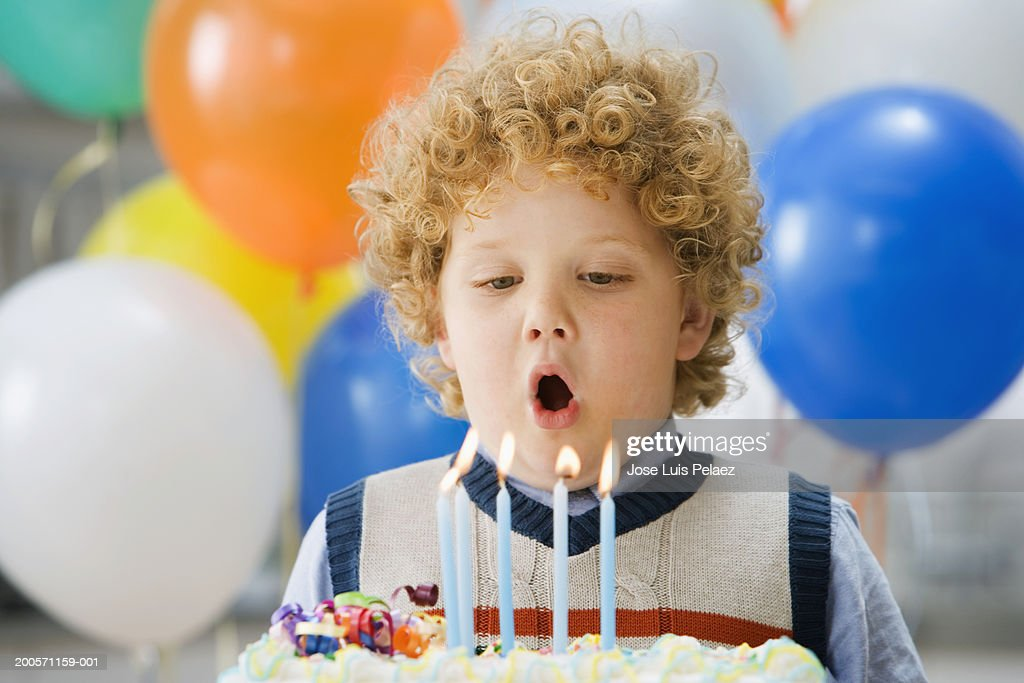 Boy (4-5) blowing out candles on birthday cake, close-up : Stock Photo