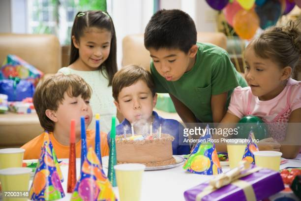 Boy blowing out candles on cake at birthday party