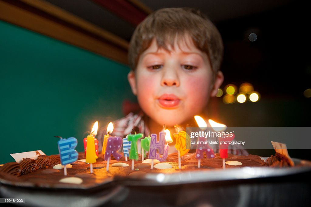Boy blowing out candles on cake : Stock Photo