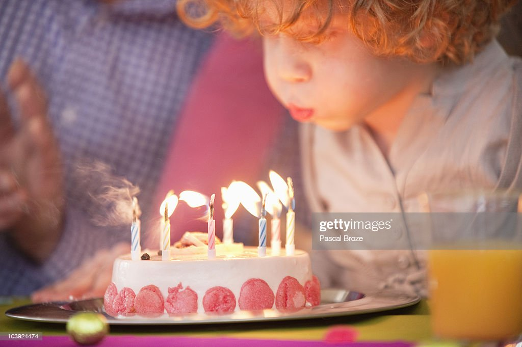 Boy blowing out candles on his birthday cake : Stock Photo