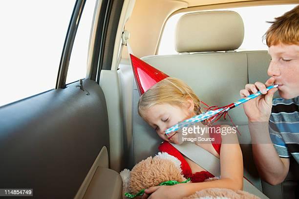 Junge Blasen Partei Gebläse auf Rücksitz des Autos