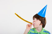 Boy blowing party horn blower