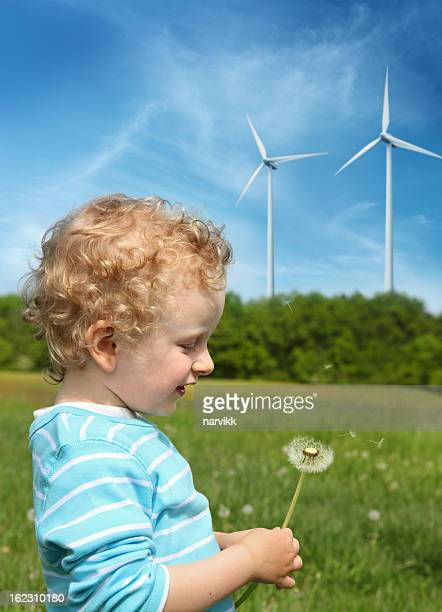 Boy blowing to dandelion and wind turbines