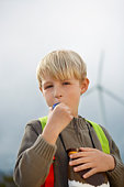 Boy (7-9) blowing toy whistle at wind farm, portrait