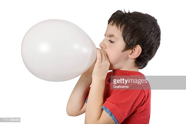 Boy blowing up a balloon