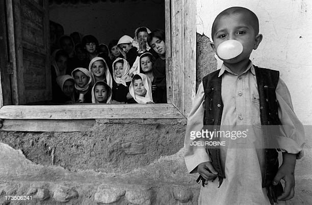 A boy blows a gum bubble as girls look out the window end of June 2001 at the SaïdaMaklifi school in Faizabad in Afghanistan's northeastern...
