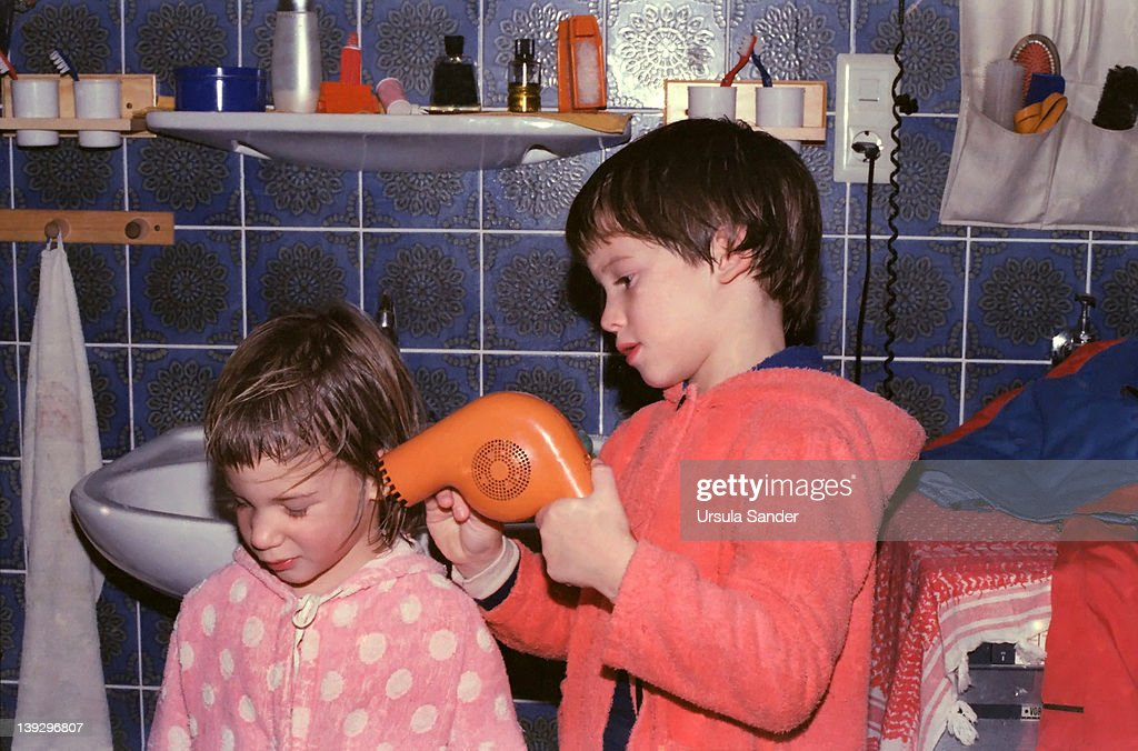 Boy blows-dry hair of his sister : Stock Photo