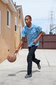 Boy bouncing basketball in yard