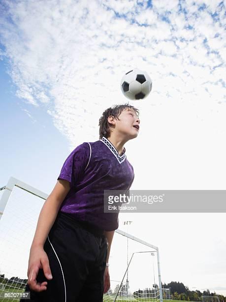 Boy bouncing soccer ball on head