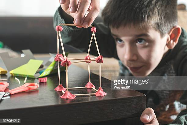 Boy building a house with modeling clay and toothpicks