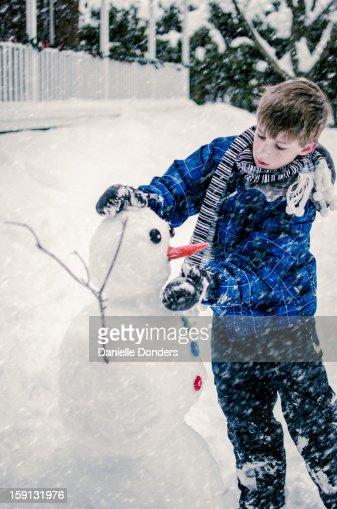 Boy building a snowman : Stock Photo