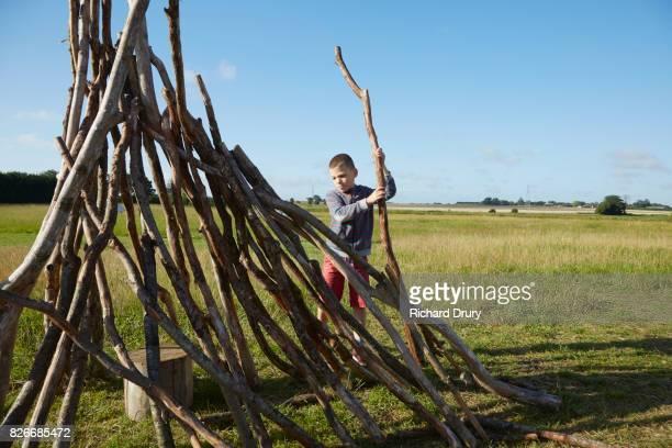 Boy building den on campsite