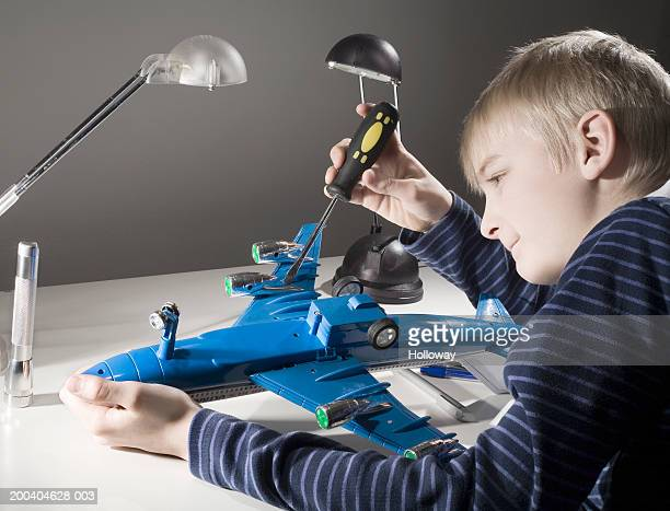 Boy (11-13) building model aeroplane, smiling