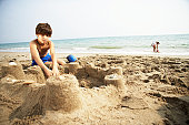 Boy (8-10) building sandcastle on beach, girl (6-8) in background