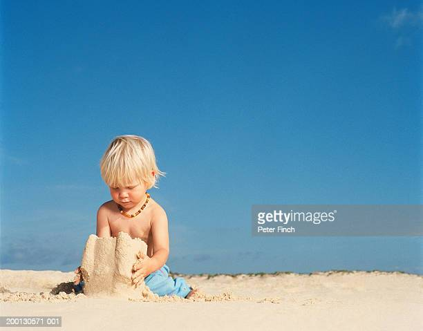 Boy (21-24 months) building sandcastle
