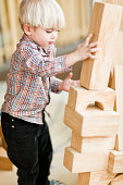 Boy building tower with wooden blocks