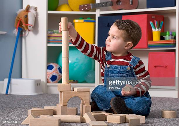 Boy Building With / Looking At Tall Wooden Toy Blocks Horizontal