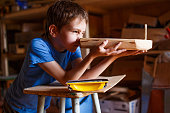 child in the workshop makes crafts. toy boat of wood