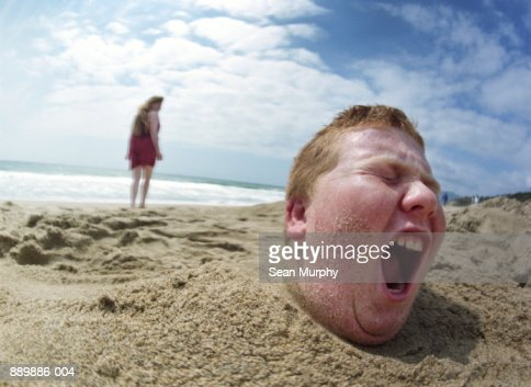A Boy Walking Away From A Girl Boy Buried In Sand Girl Walking Away Stock Photo | Getty Images