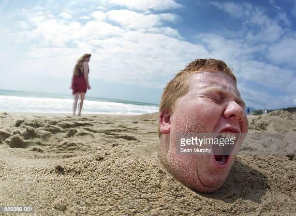 Boy (10-12) buried in sand, girl walking away