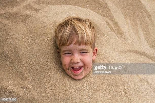 Boy buried in the sand