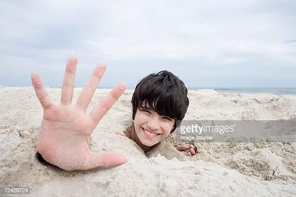 Boy buried under sand