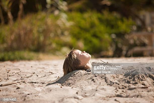 Boy buried up to his neck in the sand