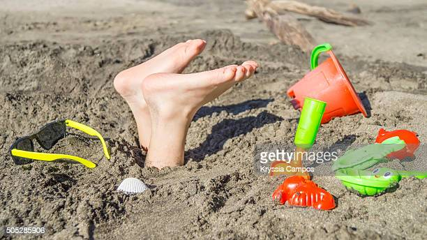 Boy buried upside down in sand at beach